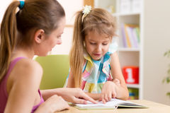 Dotter för moderundervisningbarn till att läsa Arkivbilder