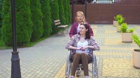 Dotter i parkerahandikappade personermodern i en rullstol arkivfilmer