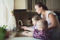 Dotter med hennes moder som tvättar deras händer i diskhon royaltyfri fotografi
