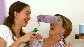 Dotter som försöker att måla hennes modernäsa med borsten lager videofilmer