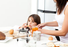dotter som ger henne driftstoppmodern till rostat bröd Royaltyfri Foto
