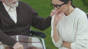 Dotter som gråter nära gammal fader i rullstolen som är deprimerad med nyheterna om cancer stock video