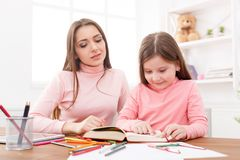 dotter som hjälper henne läxamoder royaltyfria bilder