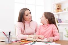 dotter som hjälper henne läxamoder royaltyfri foto