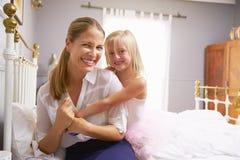 Dotter som kramar modern, som hon får klädd för arbete Royaltyfri Foto