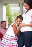 Dotter som lyssnar till gravida moders mage Royaltyfri Bild
