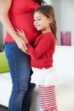 Dotter som lyssnar till gravida moders mage arkivbild