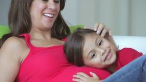 Dotter som lyssnar till gravida moders mage arkivfilmer