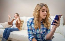 Dotter som ser en telefon och ignorerar hennes moder Arkivbilder