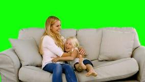 Dotterbanhoppning i armarna av hennes moder på den gröna skärmen