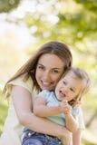 dotterholdingmoder som ler utomhus Royaltyfria Bilder
