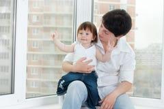 dottermoder nära fönster Fotografering för Bildbyråer