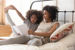 Dottern för den afrikanska mamman och för den lilla ungen läste boken i säng royaltyfria bilder