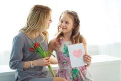 Dottern gav hennes moder en bukett av tulpan, och en vykort som göras med hennes egna, räcker lycklig motherhood royaltyfria foton