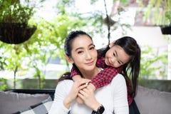 Dottern kramar hennes lyckliga moder och skratta royaltyfria foton