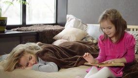 Dottern läser boken på sängen, medan mamman sover royaltyfri foto