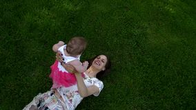 Dottern ligger med hennes moder på hennes mage stock video