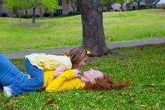 Dottern och modern som spelar att ligga på, parkerar gräsmatta Arkivfoton