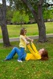 Dottern och modern som spelar att ligga på, parkerar gräsmatta Arkivbilder
