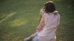 Dottern rusar in i armar för moder` s i parkera och ger henne en stor kram stock video