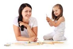 dottern tecknar henne lilla unga momblyertspennor royaltyfri foto