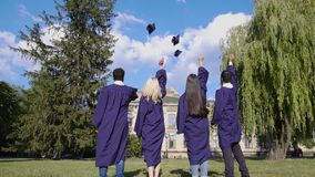 Dottorandi che gettano i cappelli quadrati su, tradizione popolare, istruzione superiore archivi video