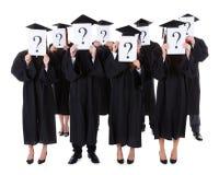 Dottorandi che mostrano i segni di domanda Fotografia Stock