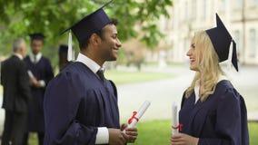 Dottorandi con la conversazione dei diplomi, alta--fiving, giorno di convocazione archivi video