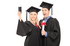 Dottorandi maschii e femminili che prendono un selfie Fotografia Stock