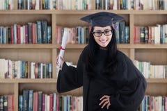 Dottorando emozionante in abito che posa nella biblioteca Immagine Stock