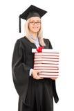 Dottorando femminile che tiene una pila di libri Fotografia Stock