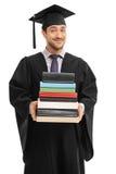 Dottorando maschio che tiene una pila di libri Immagini Stock