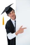 Dottorando maschio dietro un pannello ed indicare con il dito Fotografia Stock