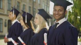 Dottorando razza mista con il diploma che sorride nella macchina fotografica, programma di scambio video d archivio