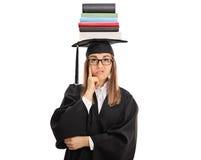 Dottorando turbato con la pila di libri su lei capa Fotografie Stock Libere da Diritti
