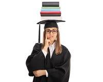 Dottorando turbato con la pila di libri su lei capa Immagini Stock