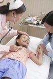 Dottore Listens al battito cardiaco della bambina, ragazza sta sorridendo Fotografie Stock