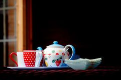 Bright pretty crockery for serving tea outdoors. A dotty teapot and cups, on a tray with a pretty sugar bowl and plates, ready to serve tea and cakes stock image