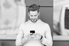 dotykaj zostać Mężczyzna z brodą chodzi z smartphone, miastowy tło Faceta use smartphone wysyłać wiadomość pobyt wewnątrz fotografia stock