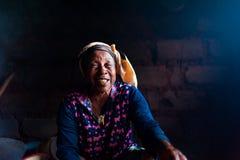 Douala Kamerun - 06 august 2018: closeup av den gamla afrikanska damen i hennes lantliga hem- kök med den traditionella klänninge arkivfoton