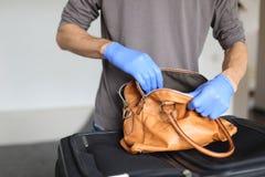 Douane bij luchthaven die veiligheidscontrole van handbagage doen royalty-vrije stock afbeeldingen