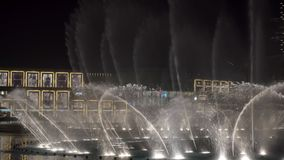 DOUBAI, DE V A e - Januari, 2018: mooi toon van dansende grote fonteinen in nacht dichtbij de de Wandelgalerijbouw van Doubai stock video