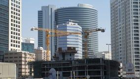 DOUBAI, DE V A e - Januari, 2018: de onvolledige bouw in een modern district van stad in de zomerdag, arbeiders en kraan stock videobeelden