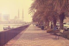 DOUBAI-VERENIGD ARABISCHE EMIRATEN OP 21 JULI 2017 De promenadepijler van het Ajman Oceaanstrand bij hete de zomerdag tegen helde Royalty-vrije Stock Afbeeldingen