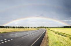 Double arc-en-ciel au-dessus de la route Photographie stock libre de droits