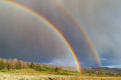 Double arc-en-ciel avec le soleil et la pluie Images stock