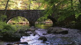Double Arch stone bridge over gently flowing Flatbrook River in Stokes State Forest, NJ, in fall