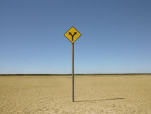 Double arrow sign on arid landscape Royalty Free Stock Images