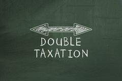 Double arrowed line showing Double taxation concept on chalkboard. Double arrowed line showing Double taxation concept on chalkboard Royalty Free Stock Photo