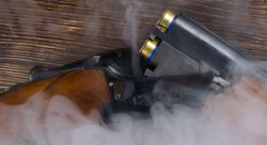 Double-barreled gun on a dark wooden background, charged with cartridge in the smoke royalty free stock photos